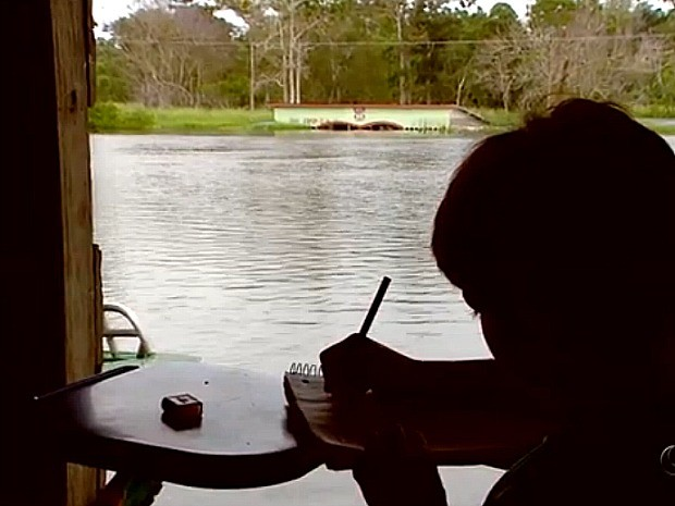 A child studying at a floating school. In the background, the roof of the old school, now flooded, is visible.